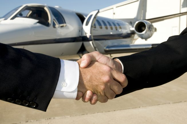 Businessmen shaking hands in front of corporate jet on ramp